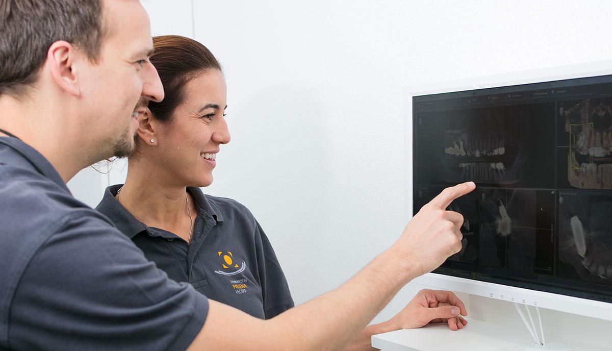 Dr. Benno Offermanns und Kollegin schauen sich eine Röntgenaufnahme vor der CMD-Therapie in Herzogenrath an.