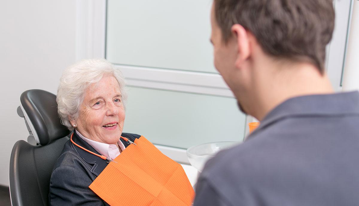 Dr. Benno Offermanns unterhält sich mit einer Patientin über Zahnimplantate aus Herzogenrath.