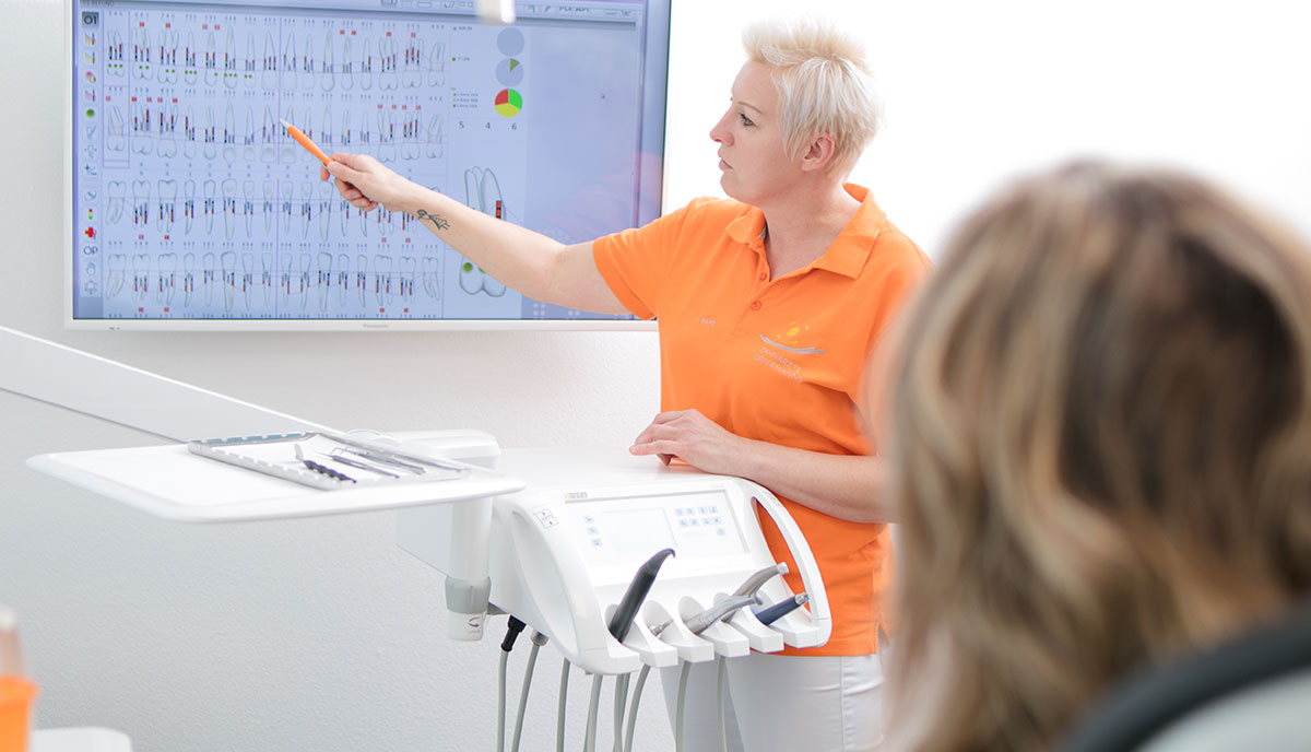 Mitarbeiterin erklärt Patientin die Wirkung der Professionellen Zahnreinigung und Prophylaxe für die Gesundheit in Herzogenrath.