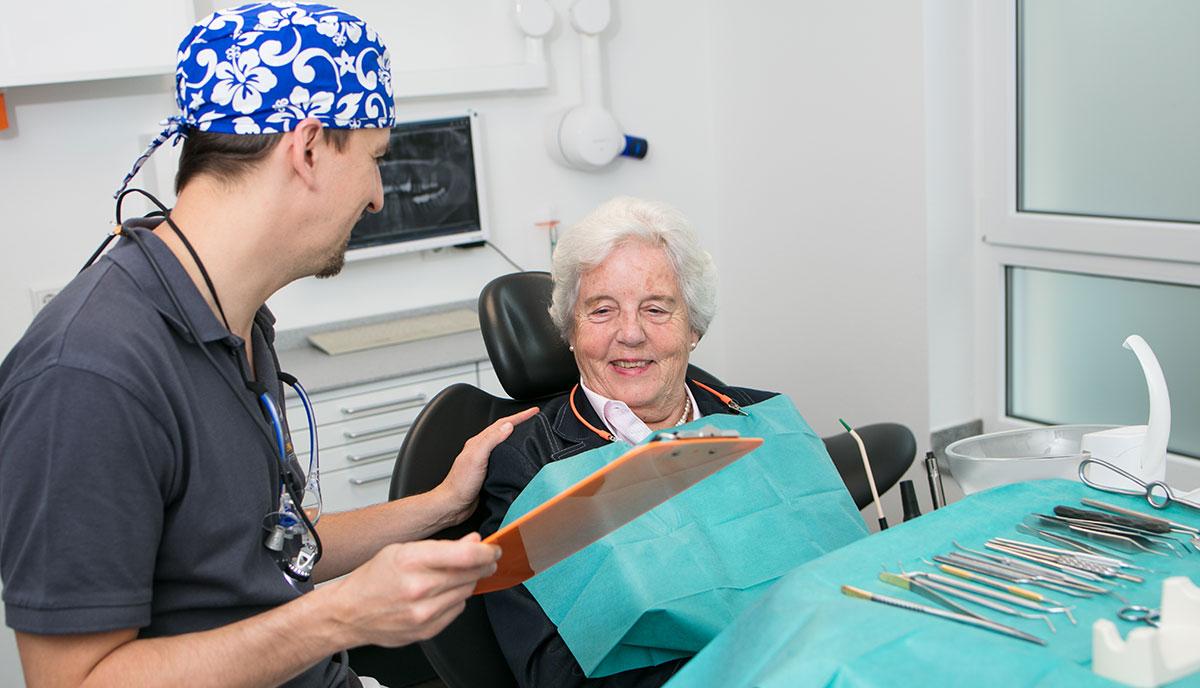 Dr. Benno Offermanns erklärt einer alten Patienten, wie schonend die Behandlung in der Oralchirurgie ist.
